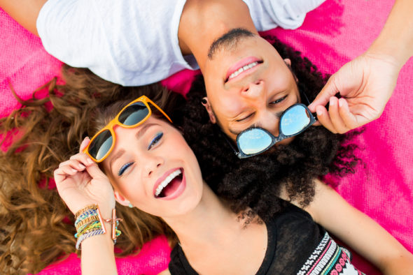 couple-laying-in-the-sun-with-their-sunglasses